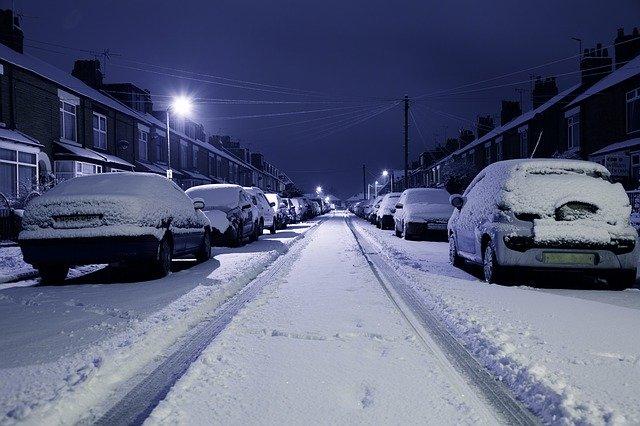 zasněžená ulice se zaparkovanými auty