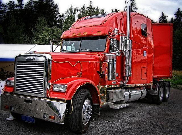 červený velký kamion stojící na cestě