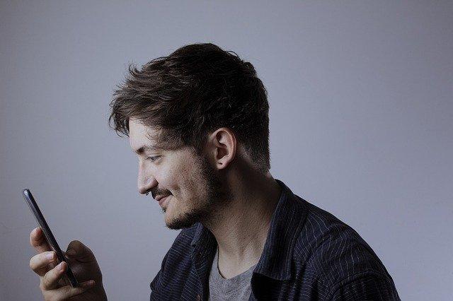 přívětivý muž za mobilním telefonem.jpg