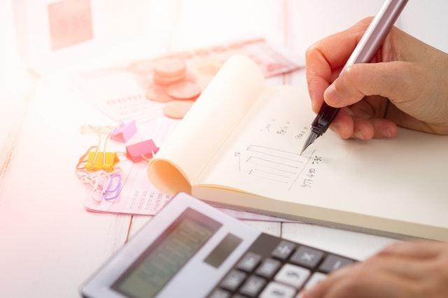 ruka drží pero, kreslí graf, vedle je kalkulačka