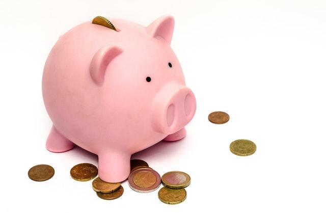 růžové prasátko jako pokladnička, vedle jsou mince eura